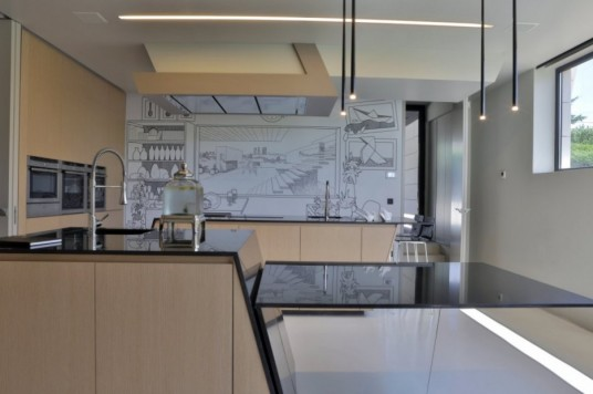Kitchen Incorporating Comic Mural Covering the Center Wall By A Cero Architects