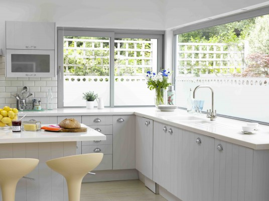 White Kitchen Design with Huge Windows Over Sink and Small Window In Other Side